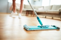 Woman showing how to clean wood floors using a dry microfiber dust mop