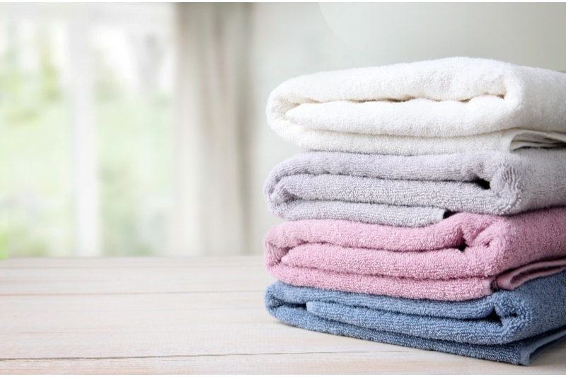 Neatly folded stack of towels on a wood table in front of a window