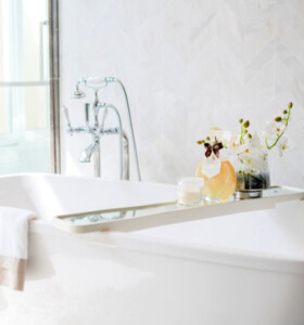 Modern white bathroom with freestanding tub and chrome faucet