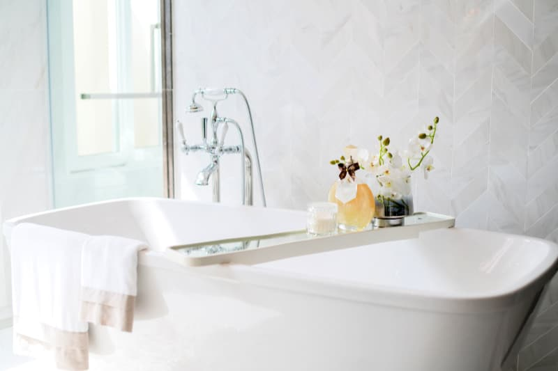 Freestanding white porcelain tub with chrome faucets and glass bath accessories
