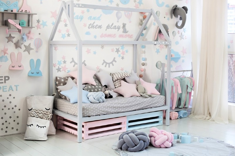Child's pastel bedroom with pastel bunnies and cartoon eyelashes on walls