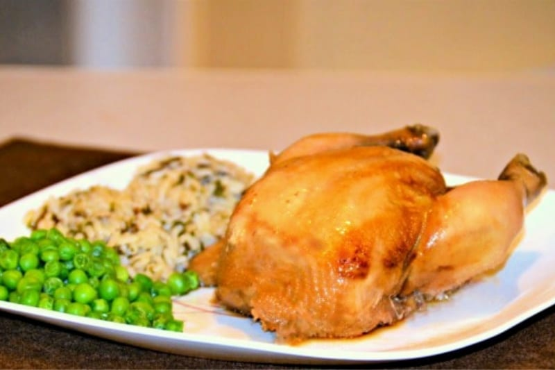 Crockpot Cornish Hens recipe served on a plate with peas and wild rice