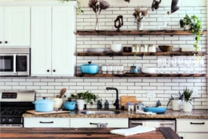 Modern white kitchen with subway tile wall and open wood shelving