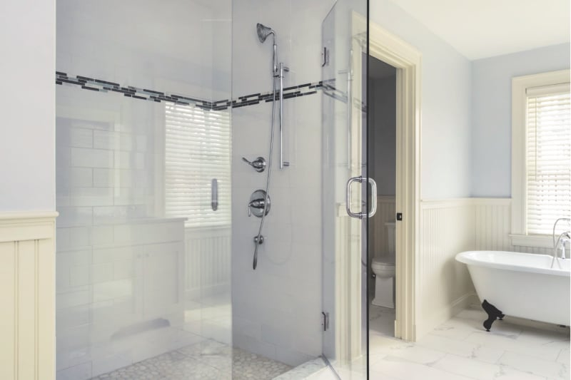 Tiled shower with glass shower doors and a claw-foot tub in a farmhouse bathroom