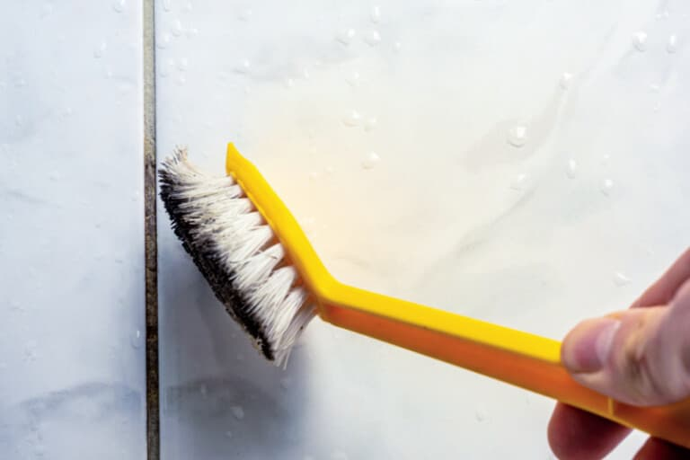 Cleaning dirty grout with toothbrush and soapy water