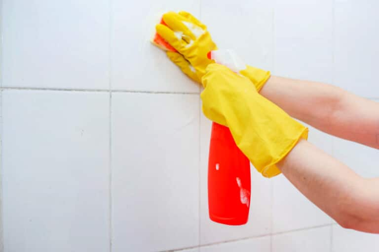 Woman wearing rubber gloves and using spray bottle and sponge to rinse homemade grout cleaner from shower wall