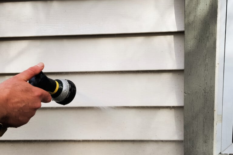 Man's hand using hose to get dirty vinyl siding clean