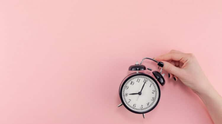 Woman holding old-fashioned alarm clock against pink background