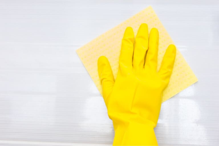 Hand in yellow rubber glove wiping shower tile with cleaning cloth