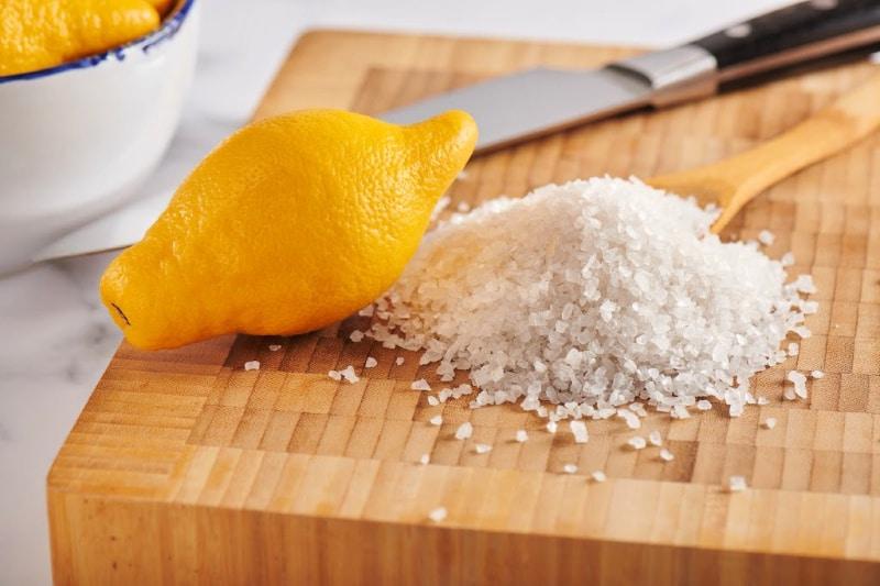 A lemon, knife, and pile of coarse salt on a wood cutting board