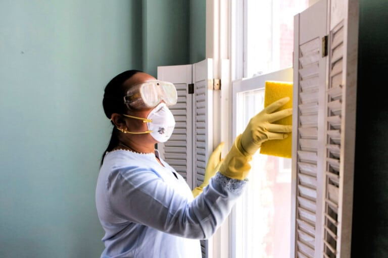 Woman wearing face mask, long sleeves, and rubber gloves as she removes mold on window and wall