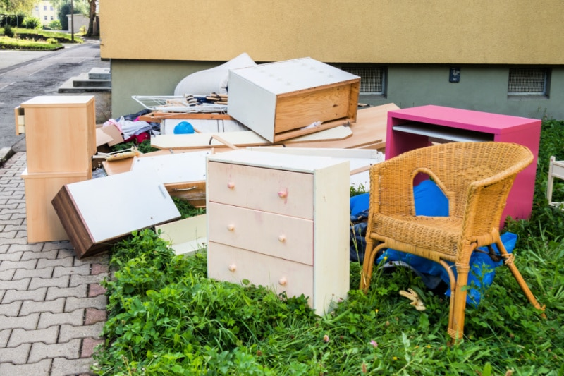 A pile of furniture and other clutter on  grass next to a curb