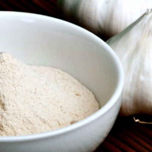 Homemade Garlic Powder Recipe in a bowl next to two heads of garlic