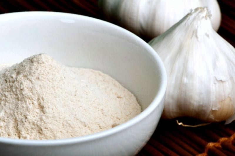 Closeup of homemade garlic powder in a bowl next to two heads of garlic