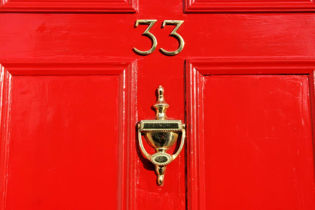 Clean and shiny brass knocker on a red front door