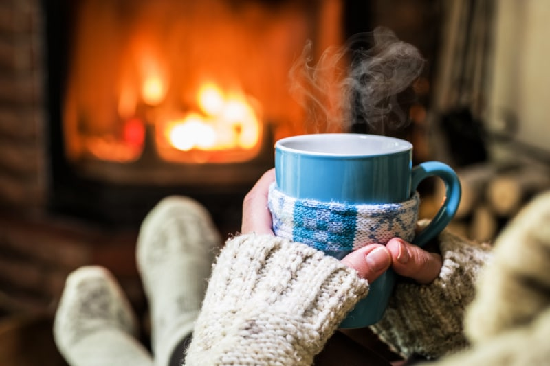 Close-up of woman's hands holding cup as she sits in front of wood burning fireplace