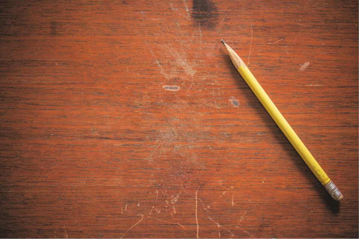 A pencil sits next to light and deep scratches in a wood tabletop waiting to be fixed