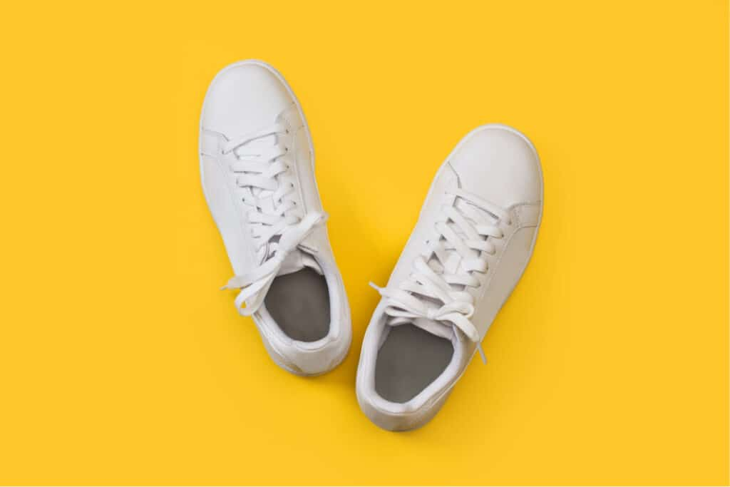 White leather tennis shoes on a yellow background