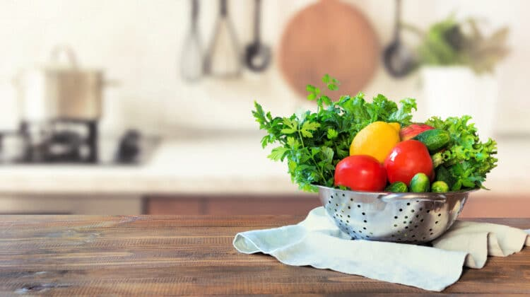 Colander filled with fruit and vegetables sitting on a towel