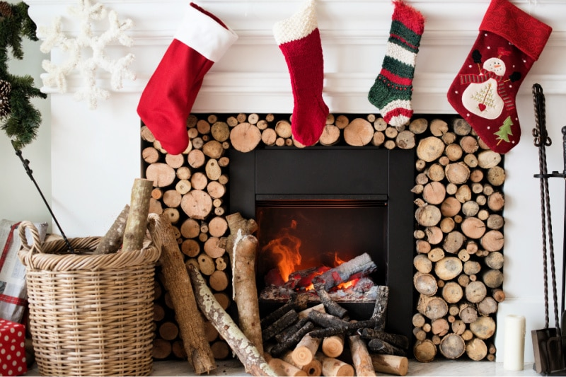 Kids Christmas stockings hanging over a wood-burning fireplace in a farmhouse-style living room