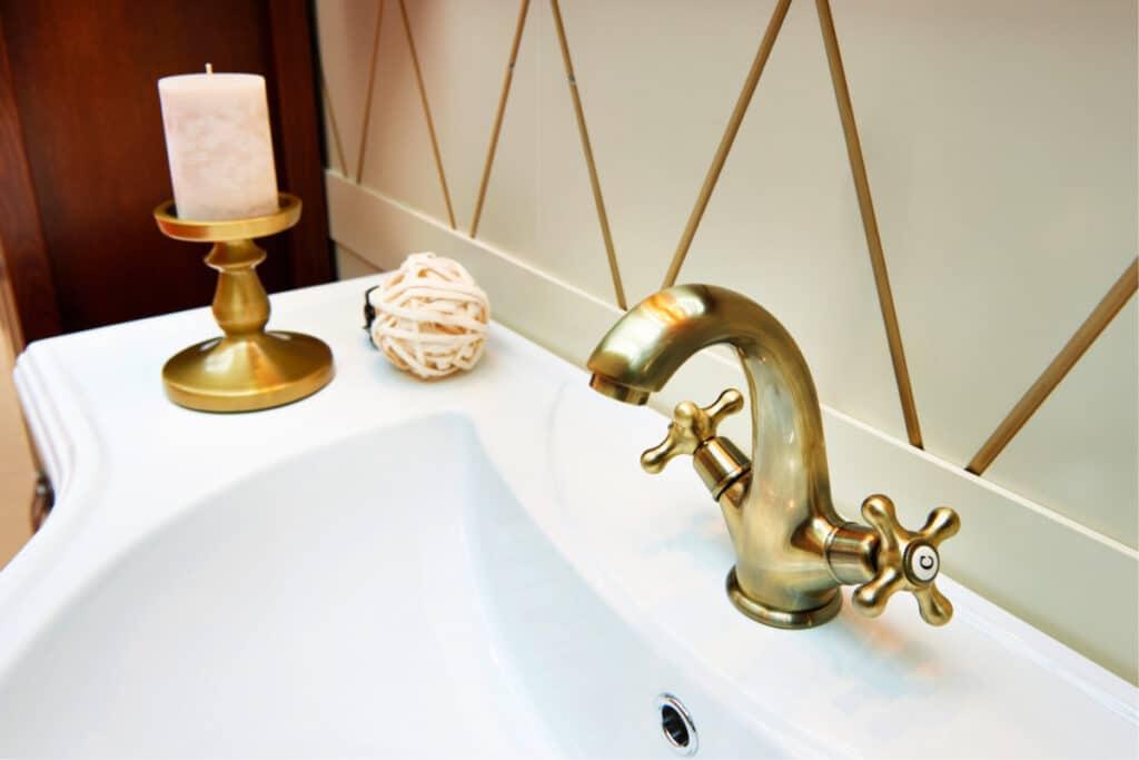 Clean brass bathroom sink faucet with a lacquered brass candlestick sitting nearby