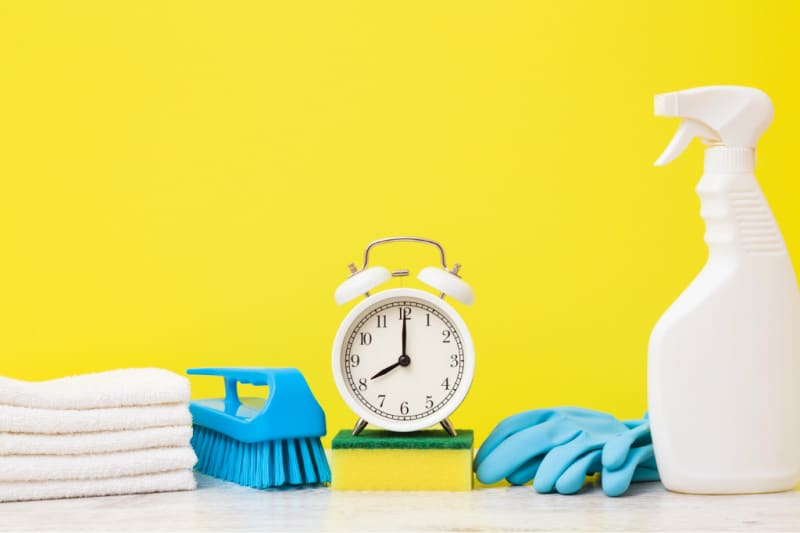 White old-fashioned alarm clock and cleaning tools set against a bright yellow background