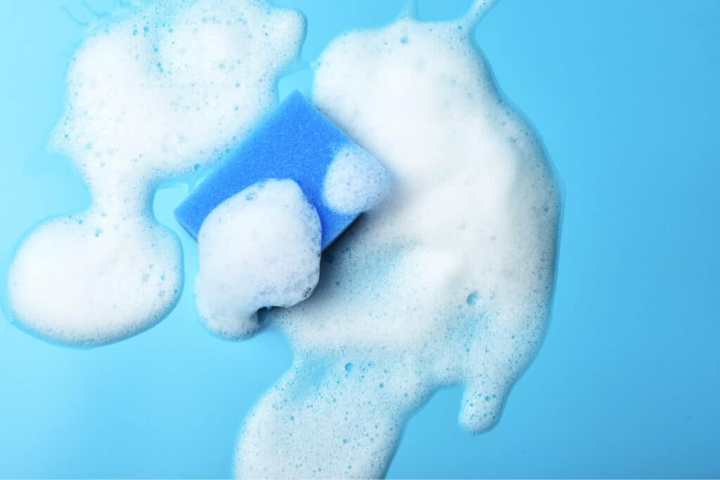Overhead shot of blue sponge and smear of soap suds