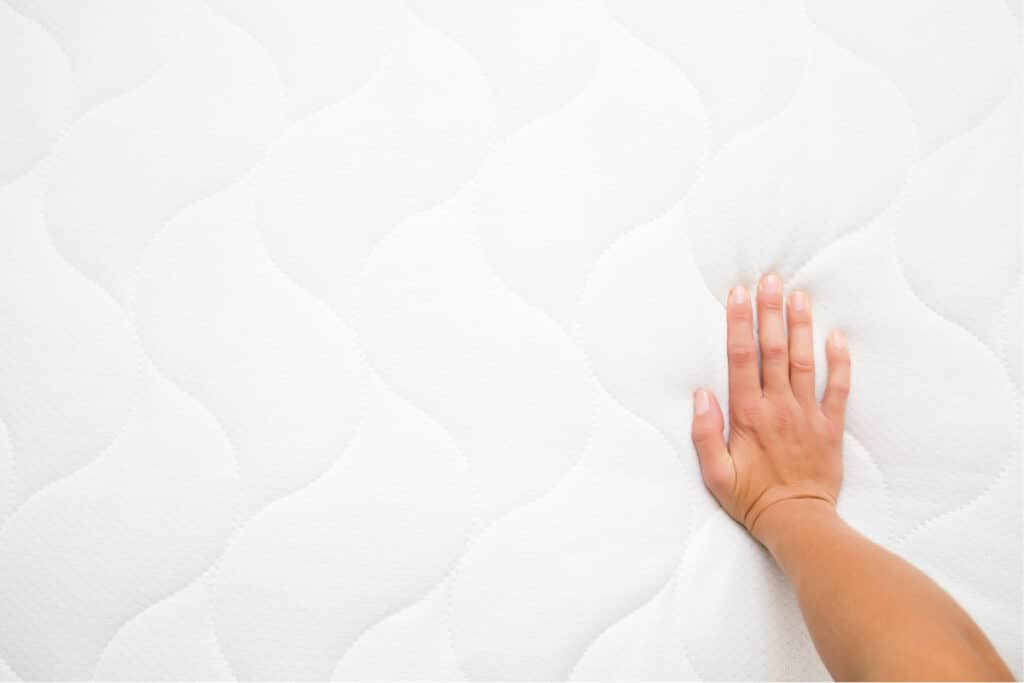 Woman's hand pressing down on a clean mattress