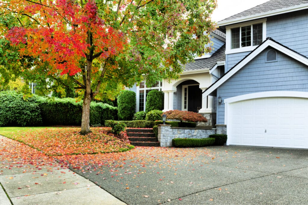 How to Get Your Home Ready for Fall -- Exterior of suburban home with leaves changing color on front yard tree