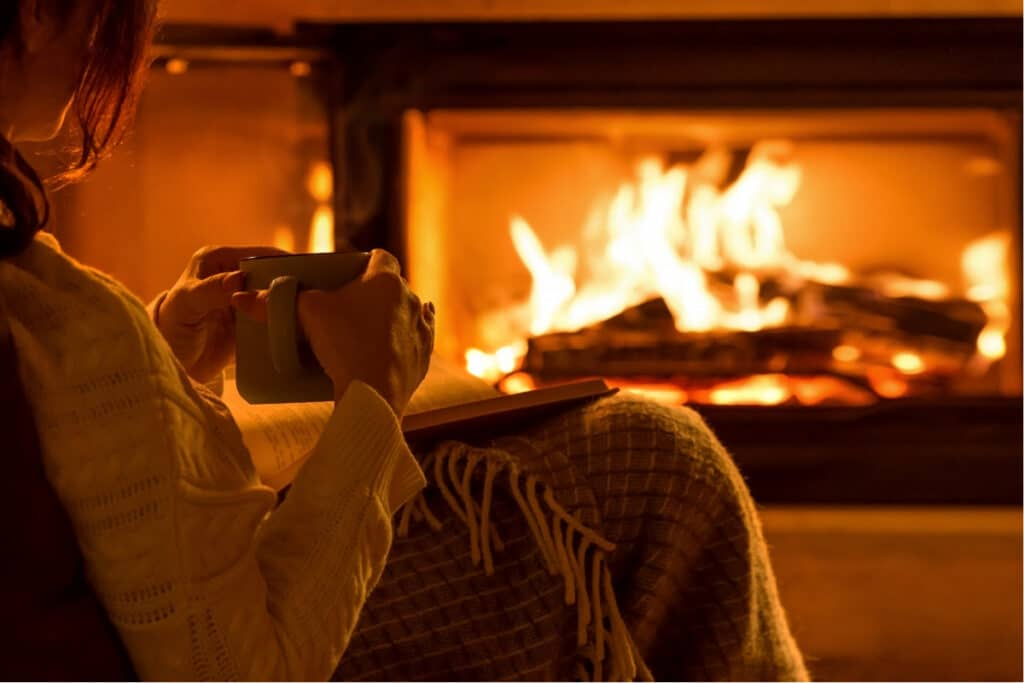 Woman sitting in easy chair holding mug of tea in front of a fireplace