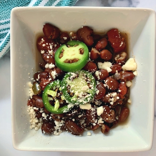 Saucy Pinto Beans Recipe served in a bowl and topped with jalapeno slices and queso fresco