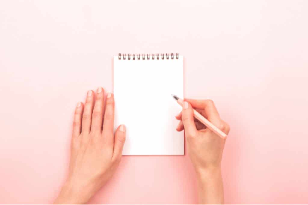 Overhead view of a woman's hands holding a white notebook and pink pencil