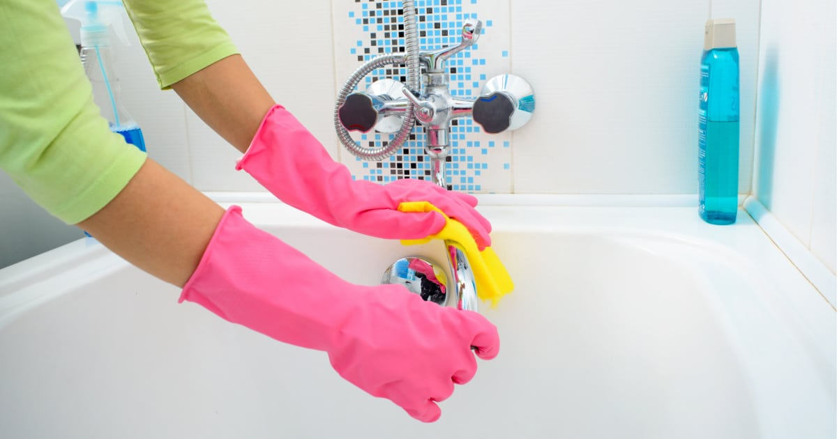 Woman wearing rubber gloves using a sponge to clean a bathtub faucet