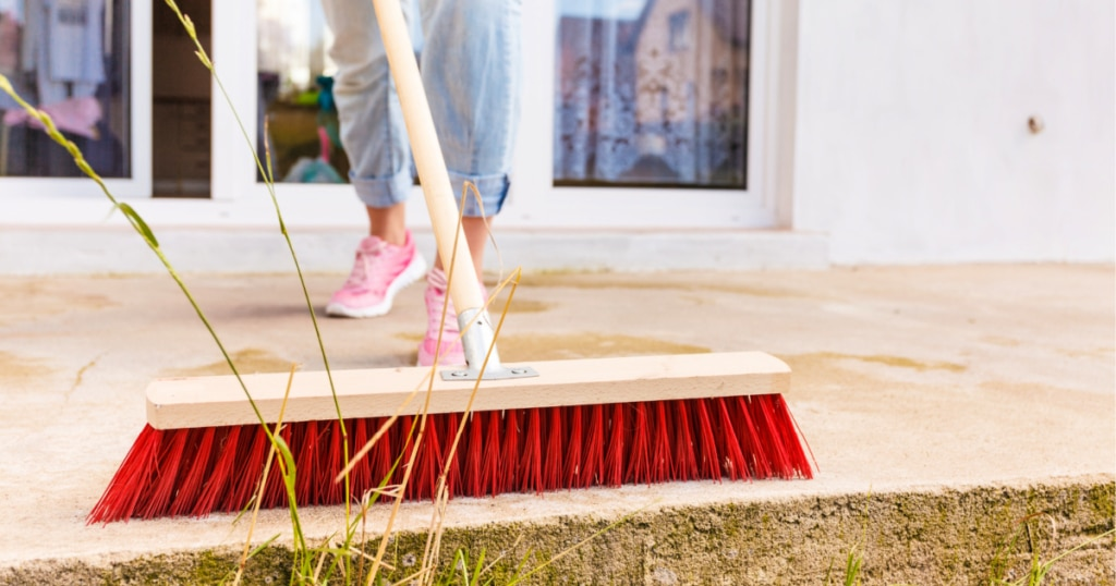 Woman using a push broom to sweep a deck outdoors