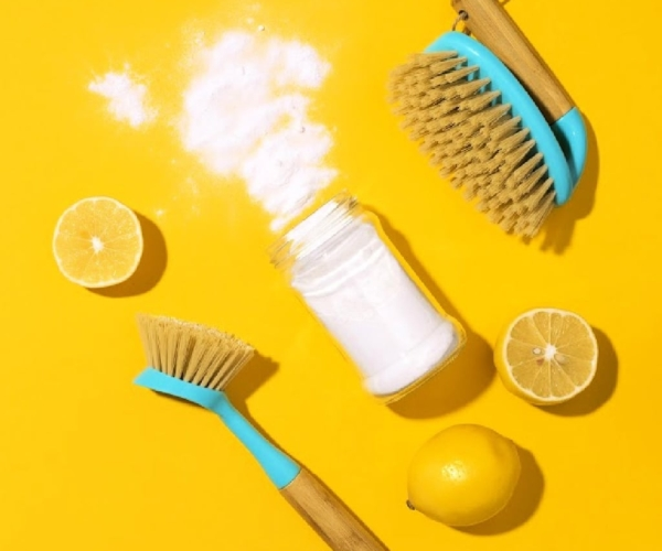 Overhead view of scrub brushes, sliced lemons and a spilled bottle of baking soda on a yellow background
