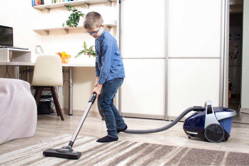 School-age boy vacuuming room as part of assigned chores and housework