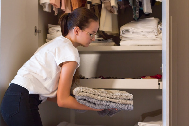 Teenage girl helping with housework by putting away folded pile of towels in linen closet