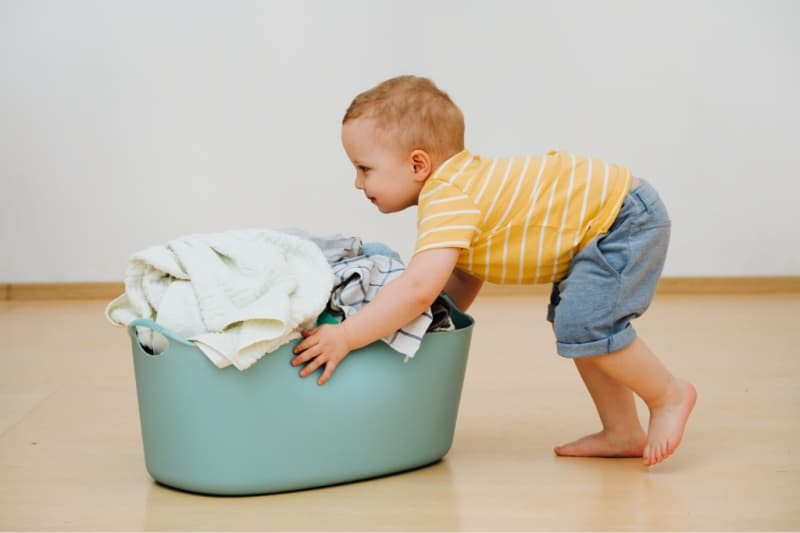Young child pushing laundry basket as part of chores