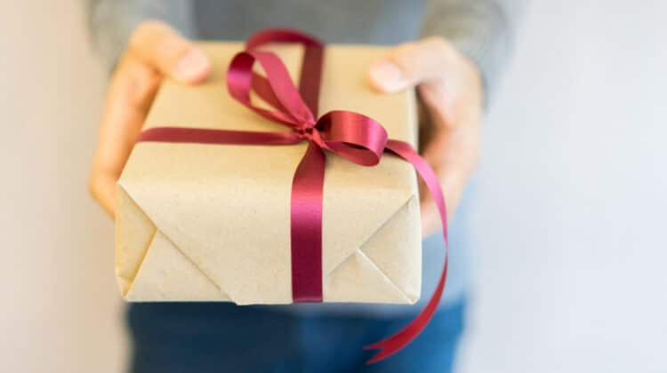 Closeup of mans hands holding a gift wrapped in plain brown kraft paper tied with a red satin bow
