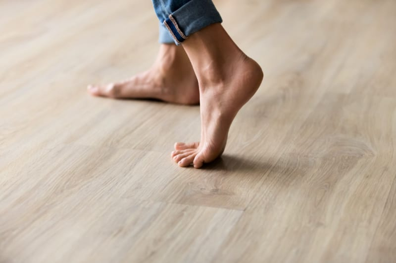 Side view of woman's bare feet in rolled up jeans walking across a clean laminate wood floor