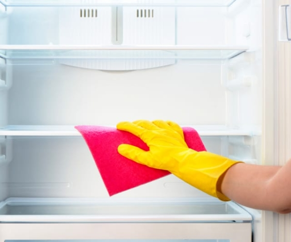 Hand in rubber glove using microfiber cloth to clean shelf in empty refrigerator