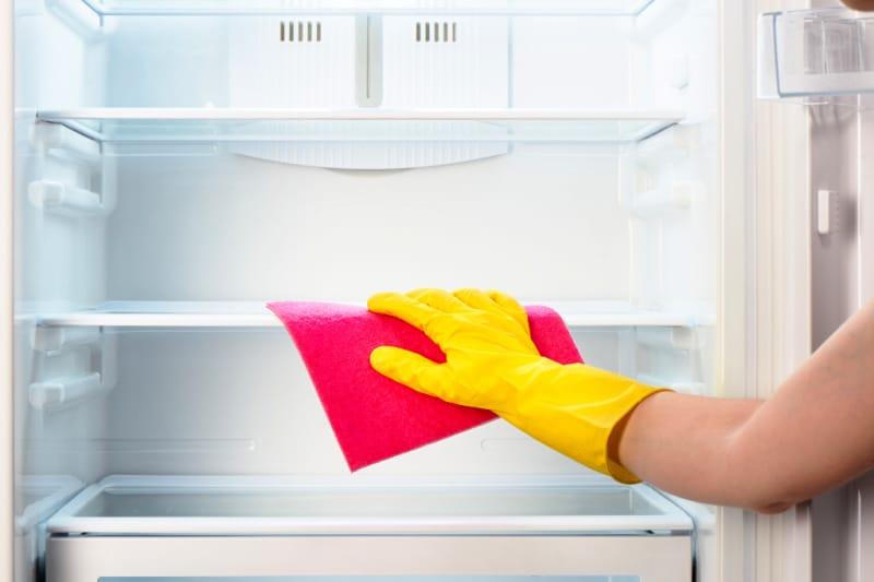 Hand in rubber glove using microfiber cloth to clean shelf in empty refrigerator