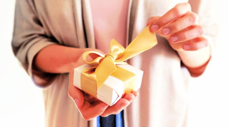 Close up of woman's hands opening a small gift tied with a ribbon
