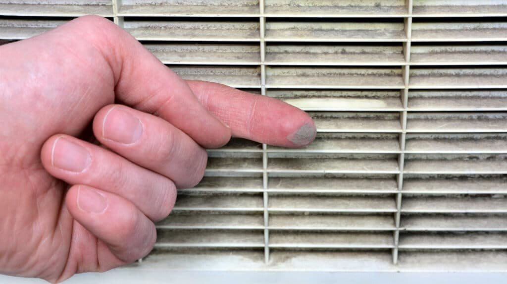 Man's hand with a fingertip covered in dust that he has swiped off of a dirty vent covering an air duct that needs to be cleaned.