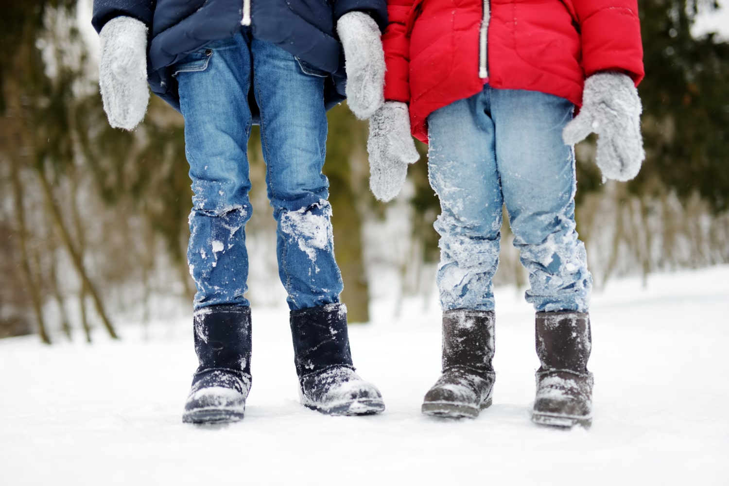 Waist-down photo of two kids in Uggs snow boots and winter clothes