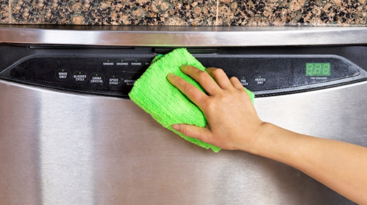Female hand holding a microfiber cloth to wipe homemade stainless steel cleaner off dishwasher front