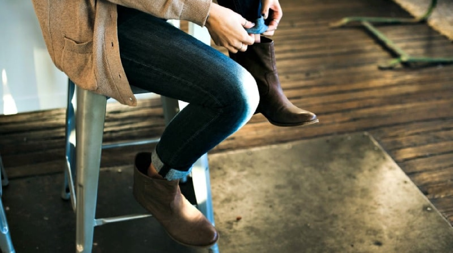 Woman sitting on stool to roll her jeans over a pair of leather ankle boots