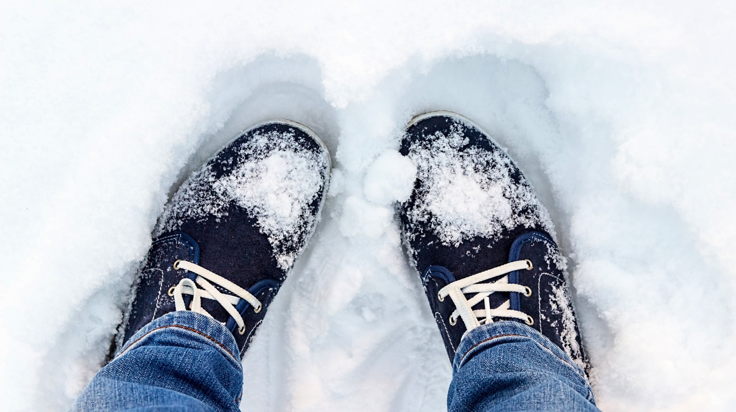 Overhead view of feet in blue sneakers standing in the snow.