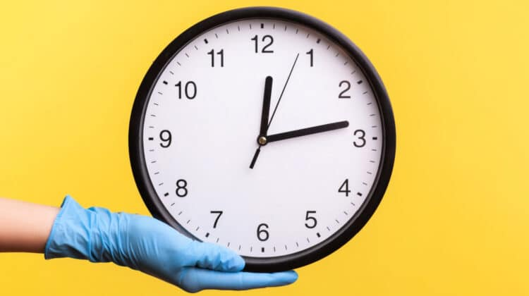 Female hand in rubber glove holding large wall clock against a yellow background