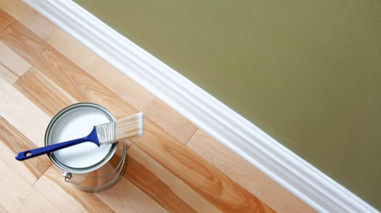 Overhead view of open can of clean brush sitting on an open can of white paint placed on a wood floor near a clean baseboard